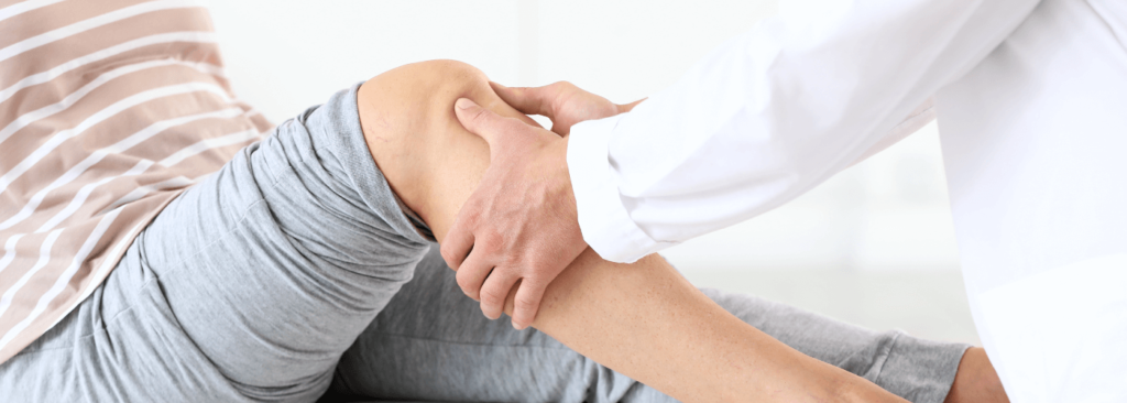 Doctor examining mature woman with joint pain in clinic