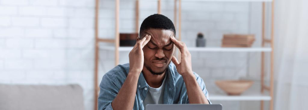 African American Businessman Having Headache Sitting At Laptop Indoor