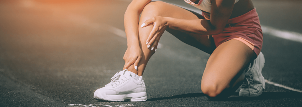Close up portrait of sporty woman having knee injury in running track., Healthcare and sport concept. Sunshine background